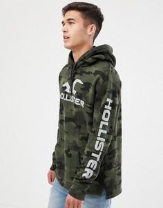 Зеленый худи с камуфляжным принтом и логотипом на рукаве Hollister Sports - Зеленый