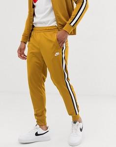 Золотистые спортивные брюки Nike Tribute