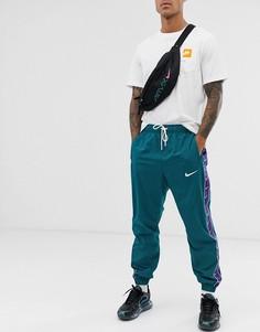 Зеленые спортивные штаны с фирменной лентой Nike-Зеленый